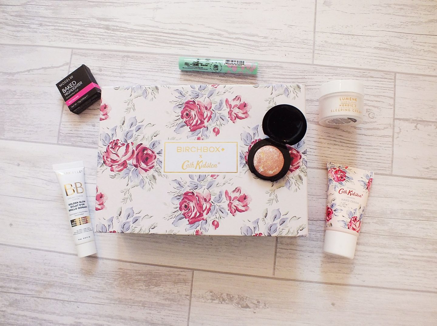 April Birchbox UK Box Contents flatlay on grey wood