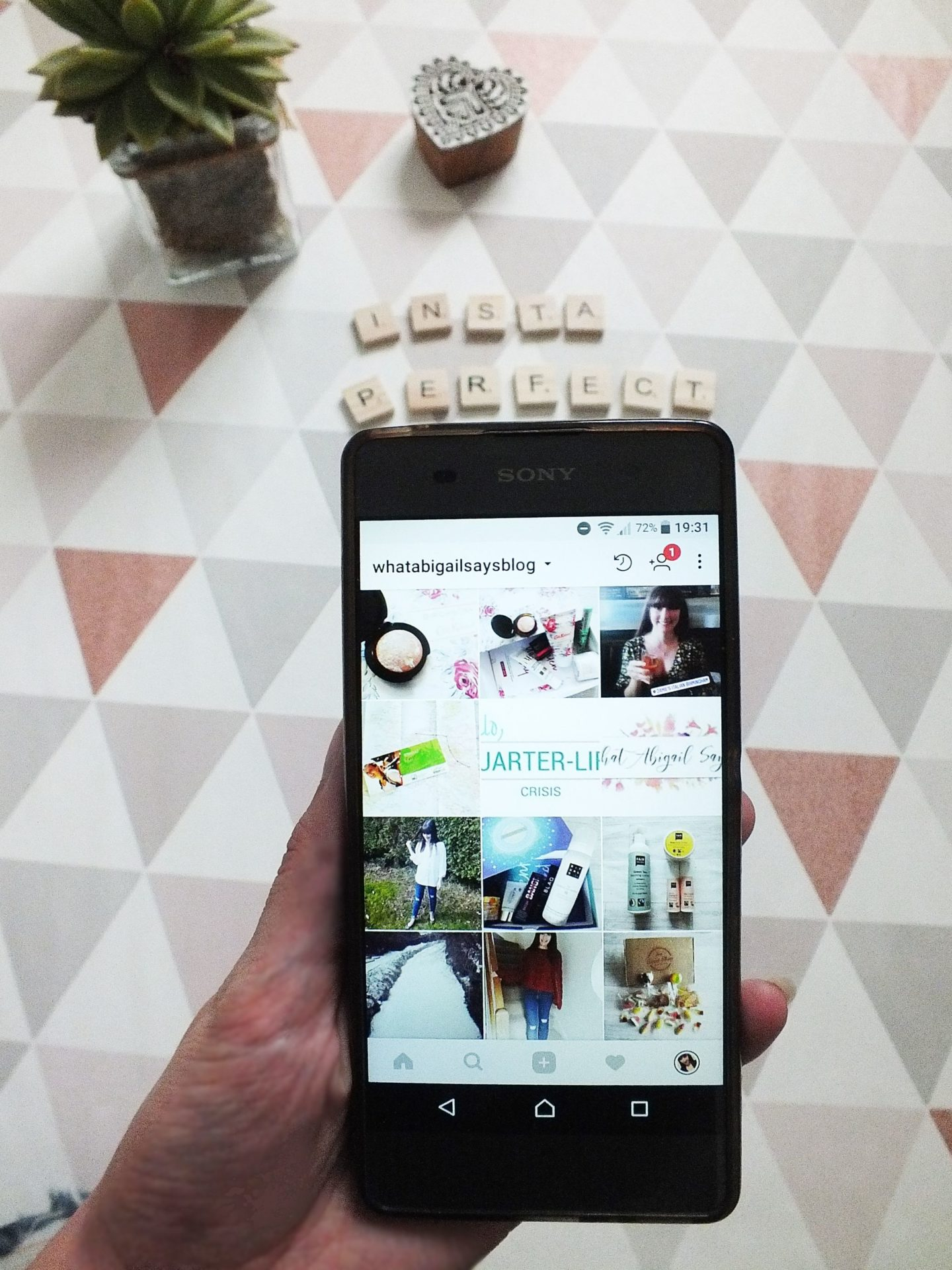 Instagram on phone over flatlay triangle background with scrabble pieces spelling Insta Perfect