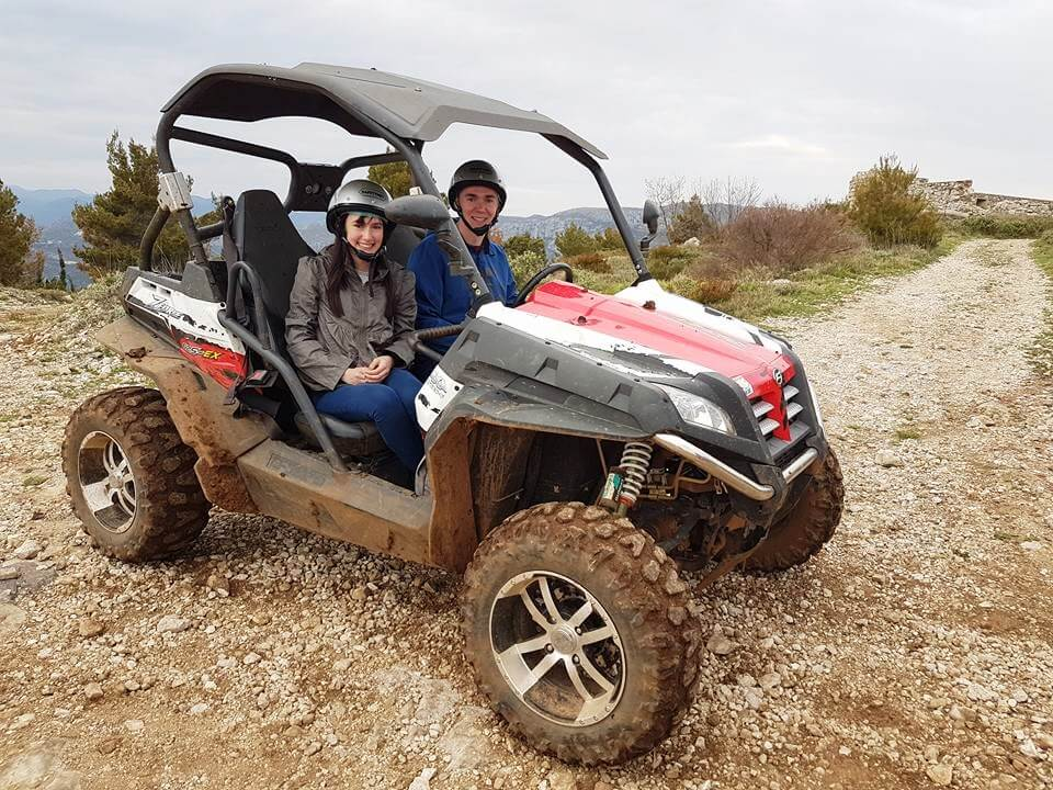 man and woman in a red and black quad bike buggy