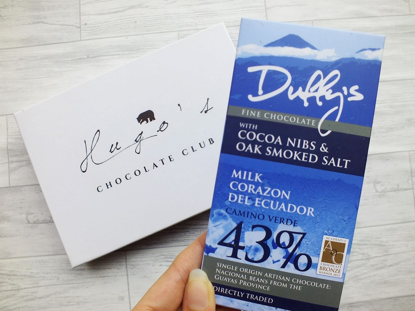 Duffys Cocoa Nibs and Oak Smoken Salt chocolate bar in blue wrapper being held up in front of Hugo's Chocolate Club box on grey wood background