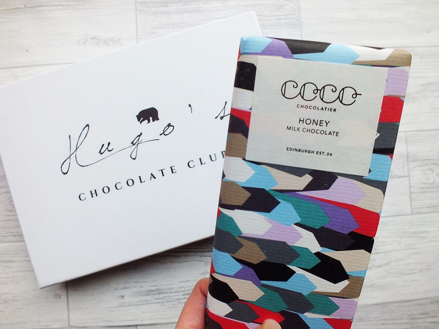 Coco Chocolatier multi-coloured chocolate bar in wrapper being held above Hugo's Chocolate Club box on grey wood background