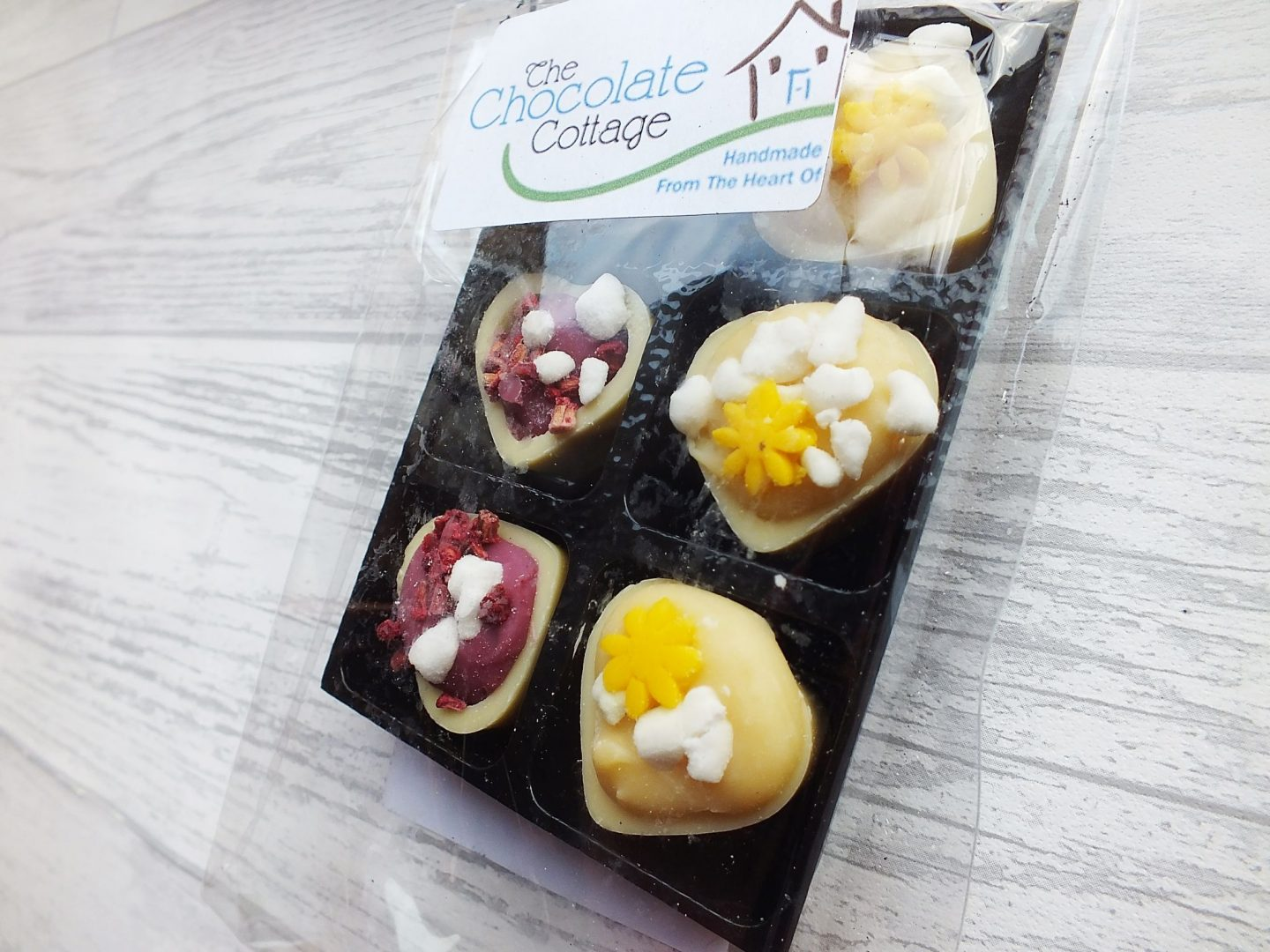 3 eton mess flavoured chocolate hearts and 3 lemon meringue flavoured hearts in packaging on grey wood background