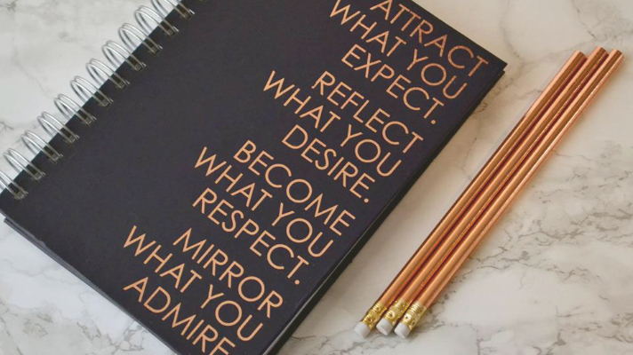Black notebook with gold text next to gold pencils on grey marble background
