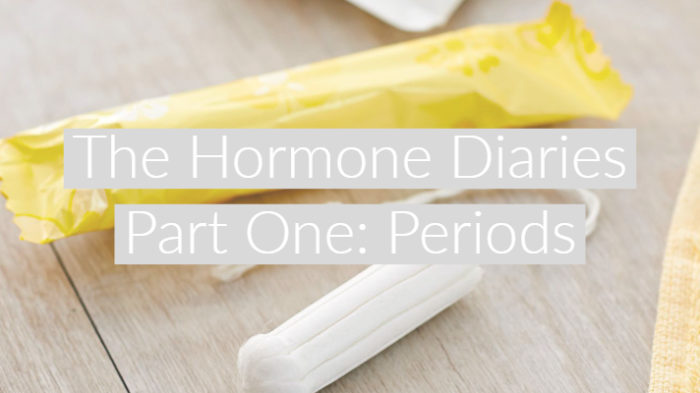 "Yellow tampon wrapper and non-applicator tampon on wood floor with text overlay ""The Hormone Diaries Part One: Periods"""