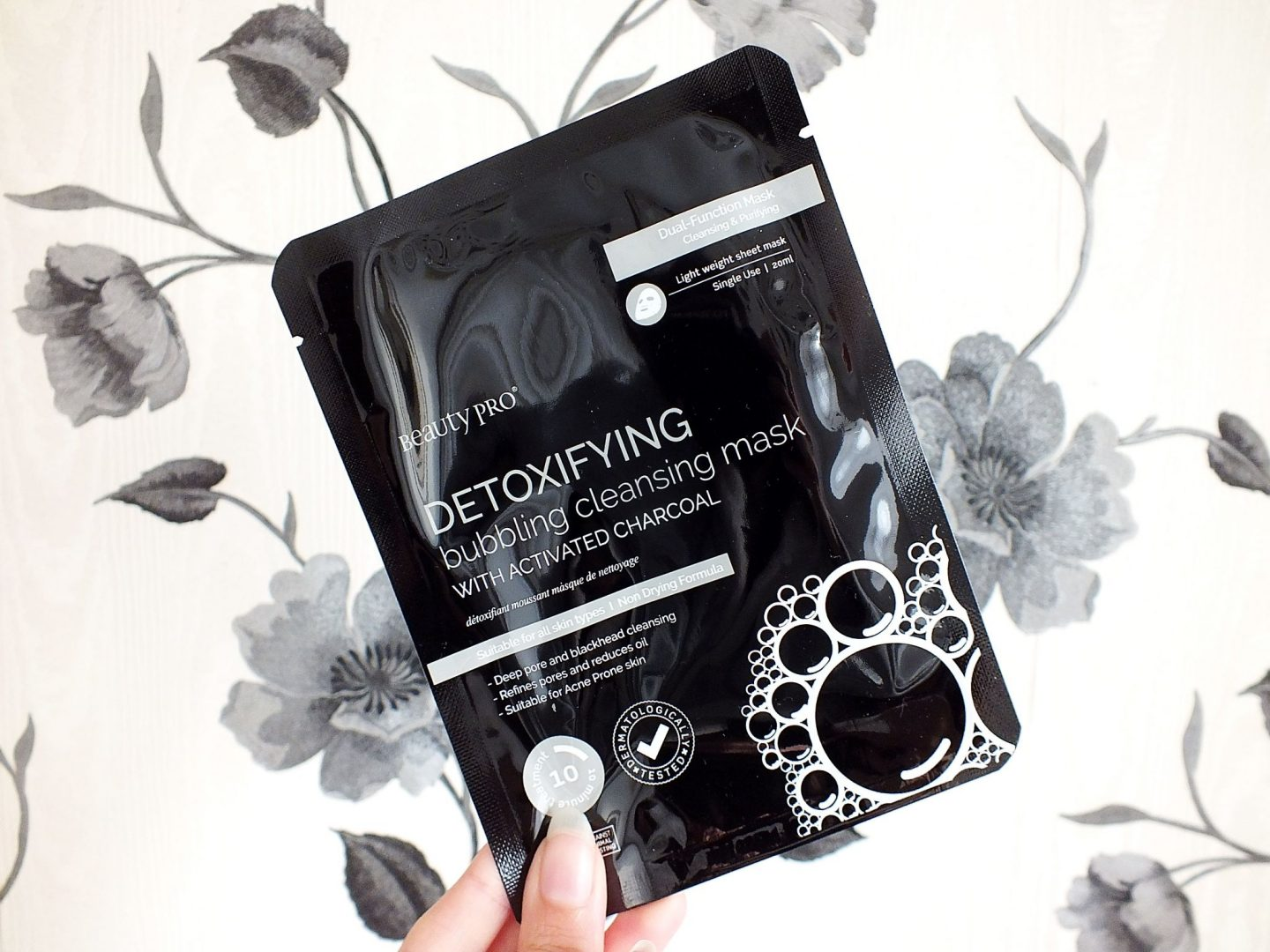 Bubbling Cleansing Sheet Mask with Activated Charcoal on a black and white floral background