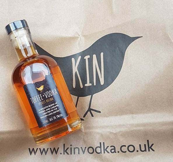 Bottle of Toffee Vodka with black label on brown paper bag with black bird logo
