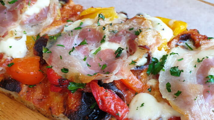 close up picture of pizza with bacon, red and yellow peppers and tomato