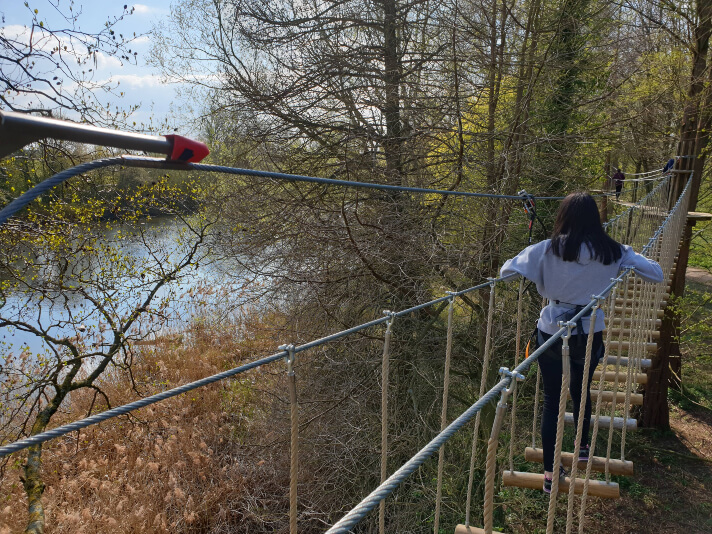girl walking across slatted bridge on high ropes course, overlooking lake