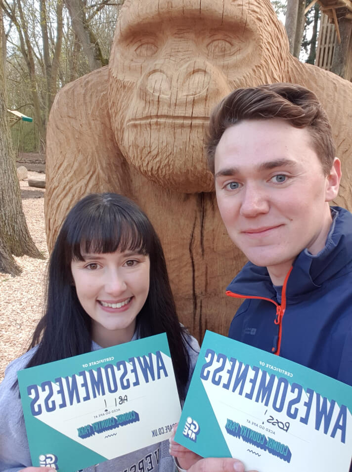 man and woman stood in front of wooden monkey statue holding blue certificates