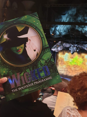 Image showing the cover of the programme for Wicked in front of Wicked set, including dragon suspended in the air