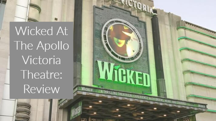 Outside of Apollo Victoria Theatre London with large green sparkly sign saying 'Wicked'