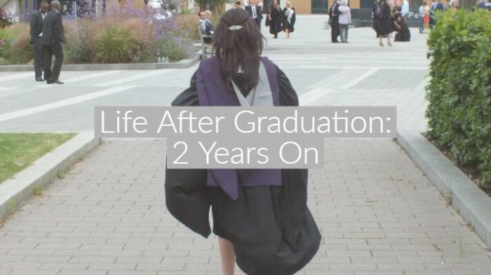 dark haired girl in black and grey graduation robes walking away from camera