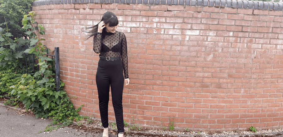 Girl stood in front of brick wall in black spotty mesh jumpsuit